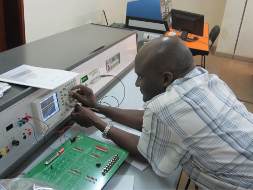 Instructor from Makerere showing the hardware his students use